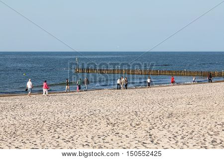 KOLOBRZEG POLAND - JUNE 19 2016: Several unidentified vacationers walks along the shoreline of the Baltic Sea and they enjoy the views that can be watched in the evening light