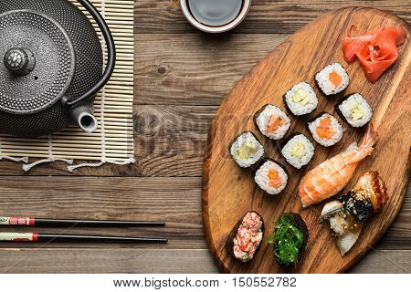 Delicious served sashimi and rolls on wooden background, view from the top