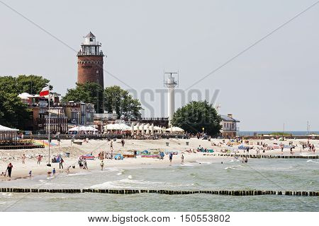 KOLOBRZEG POLAND - JUNE 19 2016: Massive lighthouse by the sandy beach where many vacationers can be seen