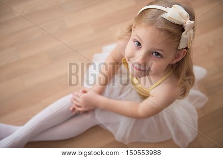 Portrait Of Smiling Pretty Diligent Ballet Girl Sitting In White Tutu. Ower View