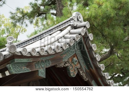 Kyoto Japan - September 14 2016: Detail of roof cover structure and of eave at Imperial palace. Set against the green of a pine tree.