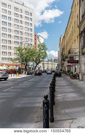 WARSAW POLAND - JUNE 11 2016: The view along the street named Zgoda in the city center. Along the street was set metal bars separating the sidewalk from the roadway.