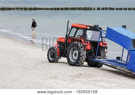 KOLOBRZEG POLAND - JUNE 21 2016: Tractor painted in red drive along the beach shore of the Baltic Sea in the distance surprised by this fact the unidentified tourist can be seen