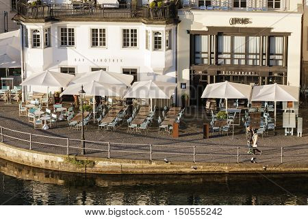 LUCERNE SWITZERLAND - MAY 06 2016: Two neighboring cafes can be seen in the morning light the tables set up outside buildings in close proximity to the banks of the River Reuss.