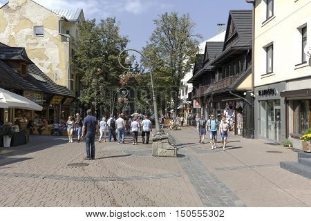 ZAKOPANE POLAND - SEPTEMBER 12 2016: Unidentified tourists walks along Krupowki street that is the most known pedestrian zone and shopping area in the city