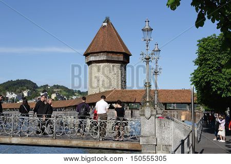 LUCERNE SWITZERLAND - MAY 09 2016: Unidentified tourists are going on the pedestrians bridge and they watch roofed Chapel Bridge and The octagonal tall tower