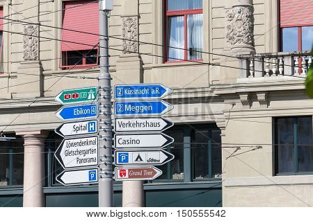 LUCERNE SWITZERLAND - MAY 04 2016: Various types of signposts that indicates diverse travel destinations in two different directions are installed on a pole in the center of town
