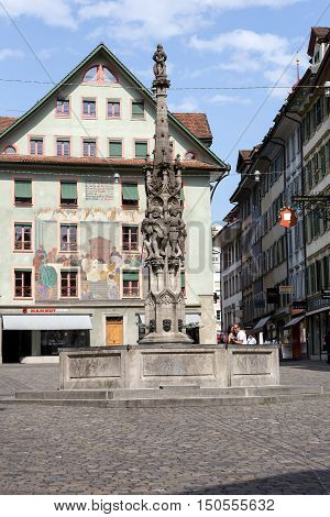 LUCERNE SWITZERLAND - MAY 10 2016: Weinmarkt Fountain that is 15th-century fountain and is surrounded by historical buildings decorated with frescos and it is located at the square in the old town