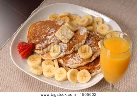 Banana Pancakes With Maple Syrup, A Strawberrry And Orange Juice