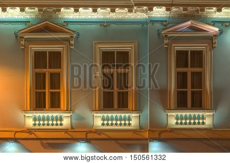 Three windows in a row on night illuminated facade of urban office building front view St. Petersburg Russia