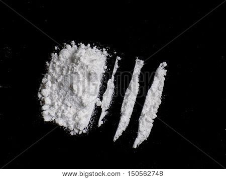 Cocaine drug powder lines and pile on black background