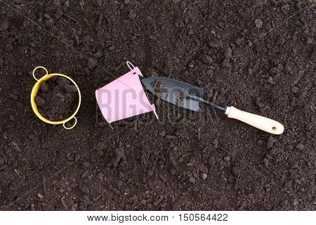 Small Pink And Yellow Pails In Rich Black Soil