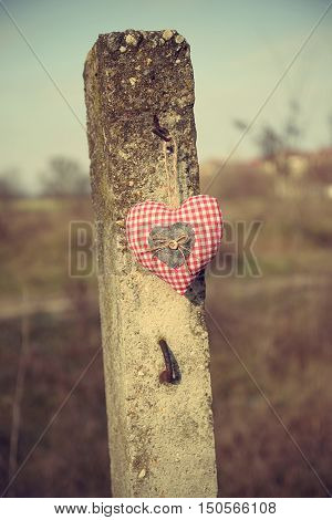 Fabric Heart Shape Hanging On A Concrete Pillar