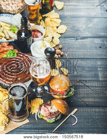 Beer and snack set. Octoberfest food frame concept. Variety of beers, grilled sausages, burgers, fried potato, corn, chips and sauces on dark wooden scorched background. Selective focus, copy space