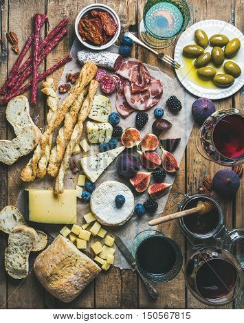 Wine and snack set with various wines in glasses, meat variety, bread, green olives, sun-dried tomatoes, figs, nuts and berries on wax paper over rustic wooden background, top view