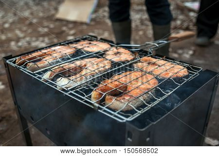 Grilled salmon steak on the barbecue at picnic.
