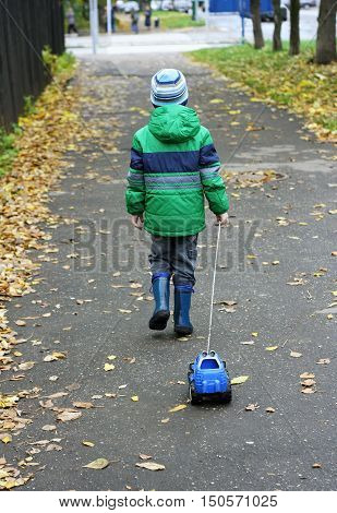Autumn walks in the fresh air. The boy in the green jacket boots and hat and children on the path strewn with leaves pulling a toy car.
