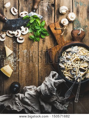Italian style dinner with copy space. Creamy mushroom pasta spaghetti in cast iron pan with Parmesan cheese, fresh basil and pepper over old rustic wooden background. Top view, vertical composition