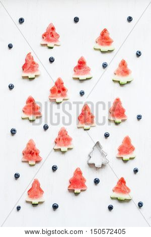 Christmas pattern. Slices of watermelon in the shape of christmas trees. Top view flat lay
