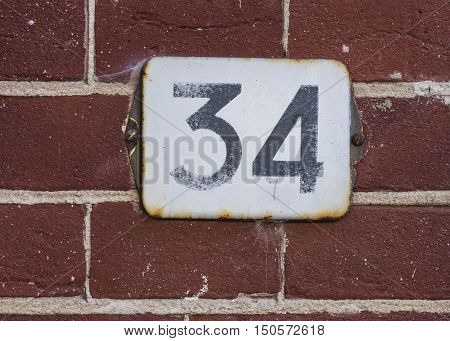 White rusty house number 34 on a red brick wall.