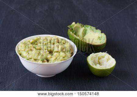 Guacamole, Avocado dip sauce on a black wooden background