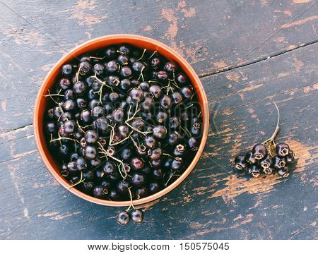 Fresh Berries Of Black Hawthorn In The Black Bowl On The Old Wooden Table Closeup. Top View
