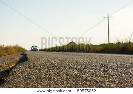 Detail of the asphalt of a country road while a car aproaches