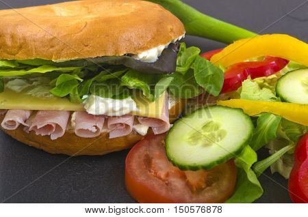 Ham Salad Bagel Bagel sliced in half with cream cheese, rolls of fresh ham and salad, served on a slate platter
