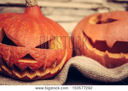 Halloween pumpkin with evil smile on rustic fabric