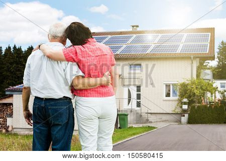 Rear View Of Senior Couple Standing In Front Of Their House