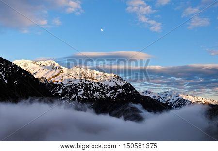 Sunrise Illuminates the Peak of Mt Phillistine and Colorful Clouds.  Temple Basin, Arthurs Pass, Canterbury, New Zealand.