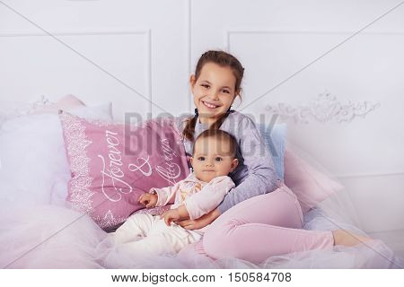 sister hugs little sister. The concept of childhood and education.