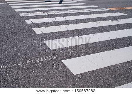 Pedestrian crossing with road marking. White lines on the dark asphalt roadJapan