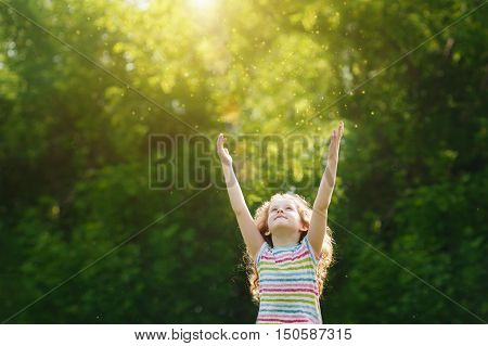 Cute little girl stretches her hand to catch sun rays. Religion donation people charity happy childhood peace world concept.