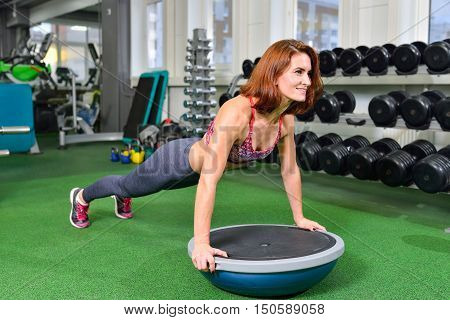 Fitness woman planking doing the body weight exercise for core strength training in gym with bosu balance trainer.
