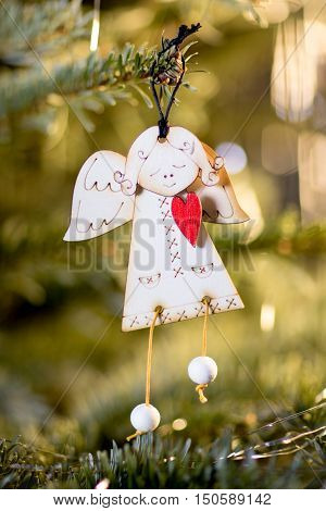 Angel holding Red Heart hanghing on a Cristmas Tree with Christmas Lights