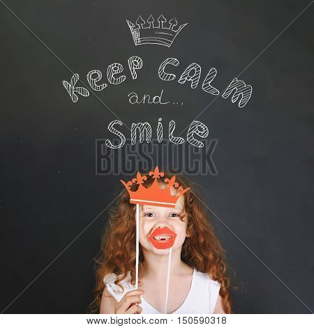 Funny girl with carnival crown and lips showing her teeth standing beside chalkboard. Keep calm and smile. Happy childhood healthy smile concept.