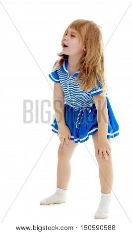 Cute little unkempt girl in a short blue dress. Girl looking to the side with his hands on his knees.Isolated on white background.