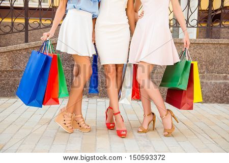 Close Up Of Three Beautiful Shoppers Showing Their Smooth Legs