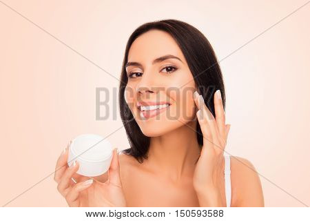 Young Attractive Girl Applying Cream On Her Face