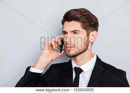 Young Serious Bearded Businessman Talking Of Phone With Colleague