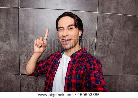 Portrait Of Funny Hispanic Having Idea And Showing Tongue