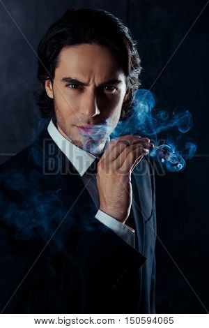 Closeup Portrait Of Brutal Man  Holding A Cigar With Smoke In Hand