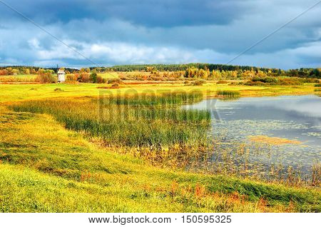 Autumn picturesque landscape- autumn view golden autumn valley and small lake. Autumn natural landscape of autumn nature in sunny autumn weather.Autumn colorful valley landscape in golden autumn tones