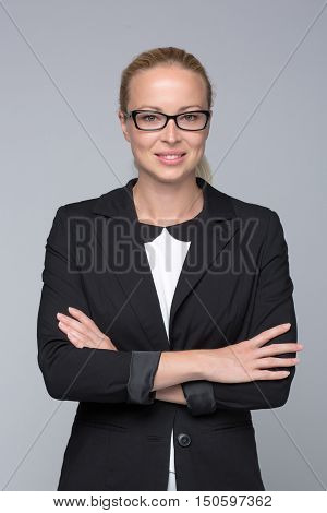 Portrait of beautiful smart young businesswoman in business attire wearin black eyeglasses, standing with arms crossed against gray background.