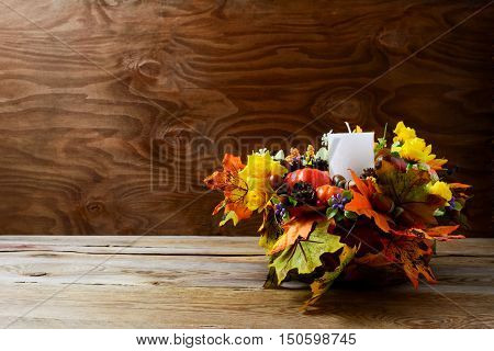 Thanksgiving decoration with silk fall leaves on rustic background. Thanksgiving greeting with fall decor. Fall centerpiece. Thanksgiving background. Copy space.