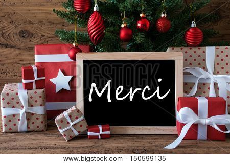 Colorful Christmas Card For Seasons Greetings. Christmas Tree With Red Balls. Gifts Or Presents In The Front Of Wooden Background. Chalkboard With French Text Merci Means Thank You