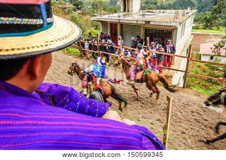 Todos Santos Cuchumatan, Guatemala - November 1 2011: Traditionally dressed locals watch drunken jockeys race up & down dirt track on horseback in unique All Saints' Day celebration in highland town