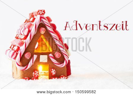 Gingerbread House In Snowy Scenery As Christmas Decoration With White Background. Candlelight For Romantic Atmosphere. German Text Adventszeit Means Advent Season