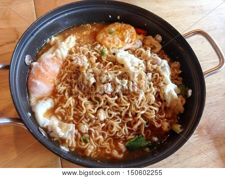 Instant noodles with minced pork and boiled egg in black bowl.